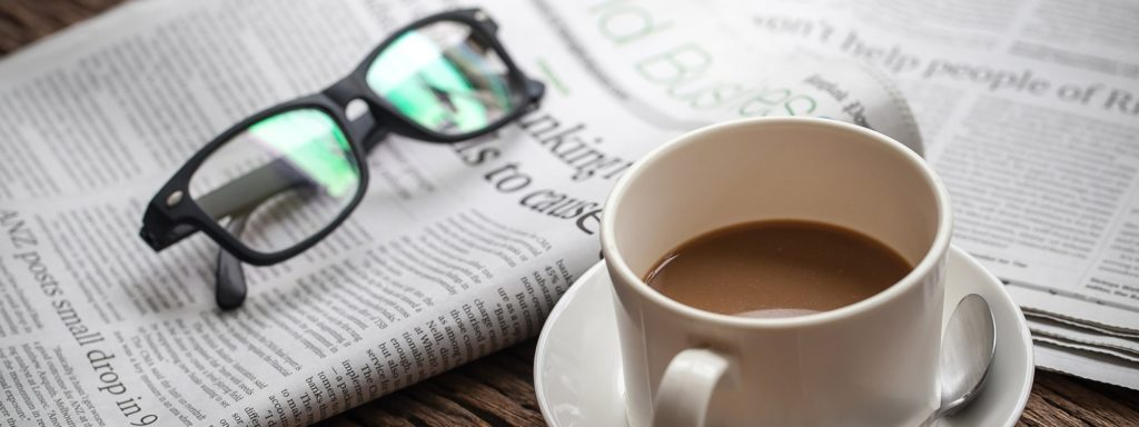 Coffee table with a newspaper, glasses, and a cup of coffee